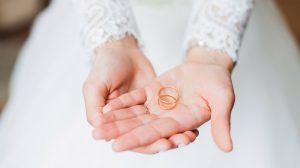 Bride wearing white dress holding wedding rings on the palm of her hand
