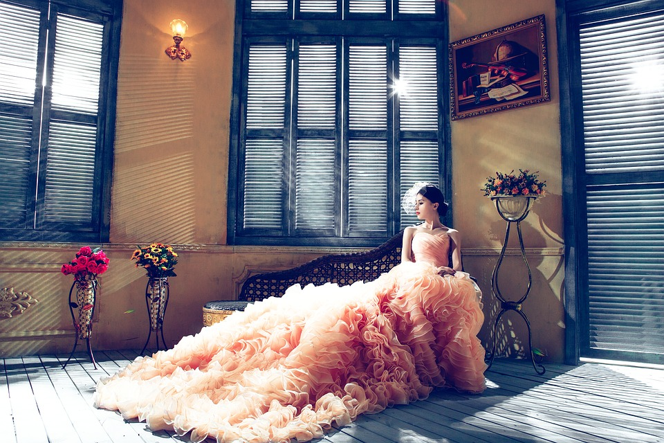 Bride wearing wedding dress siting on a chair