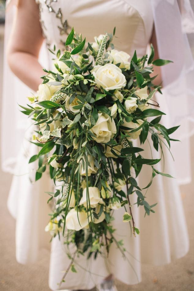 Bride holding beautiful rose cascade bouquet