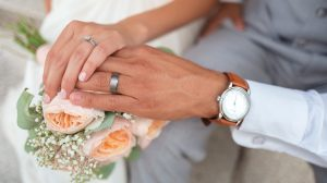 Couple wearing wedding band holding hands