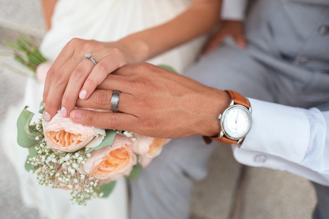 Couple wearing wedding band holding hands