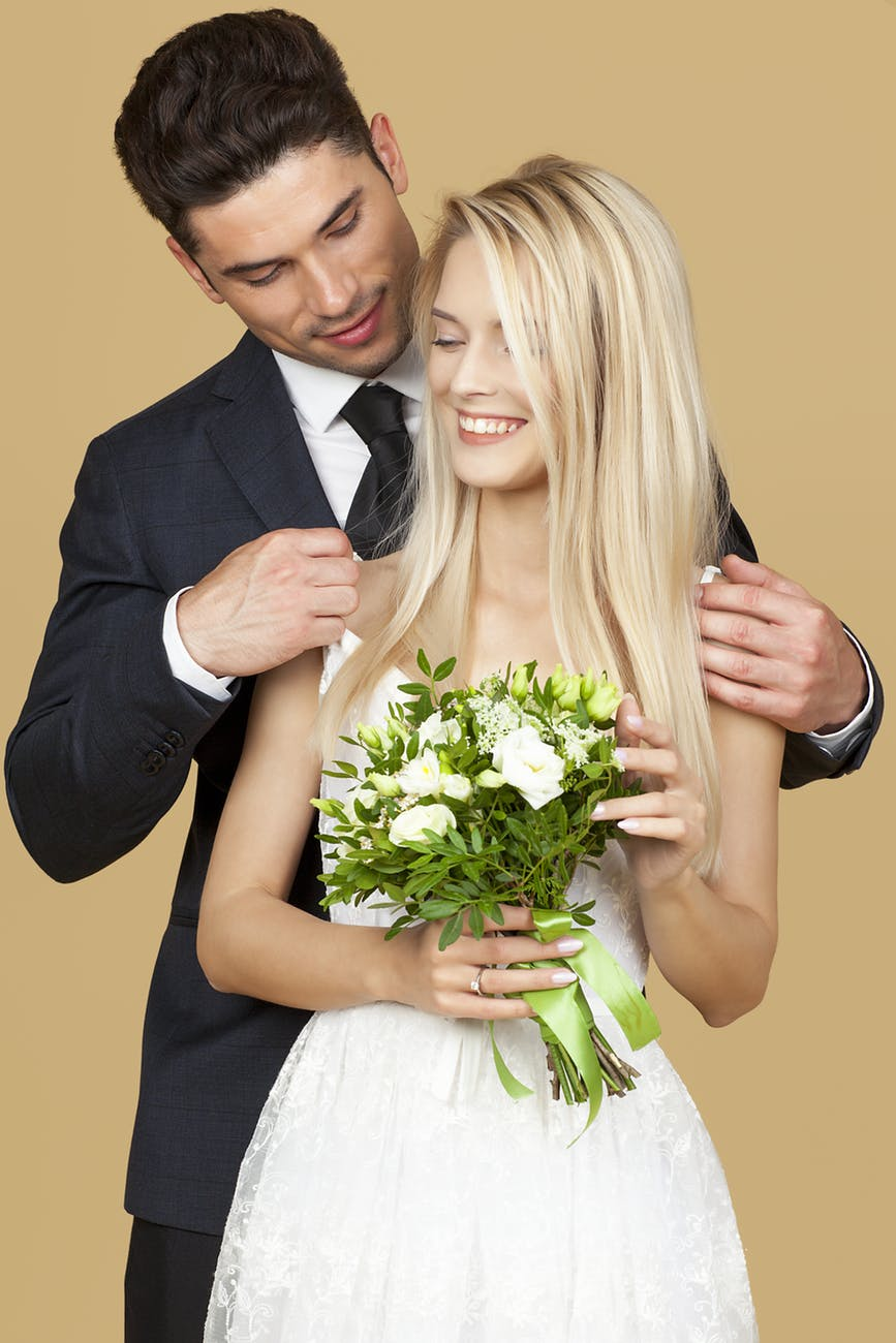 Bride holding hand tied bouquet with groom on the back