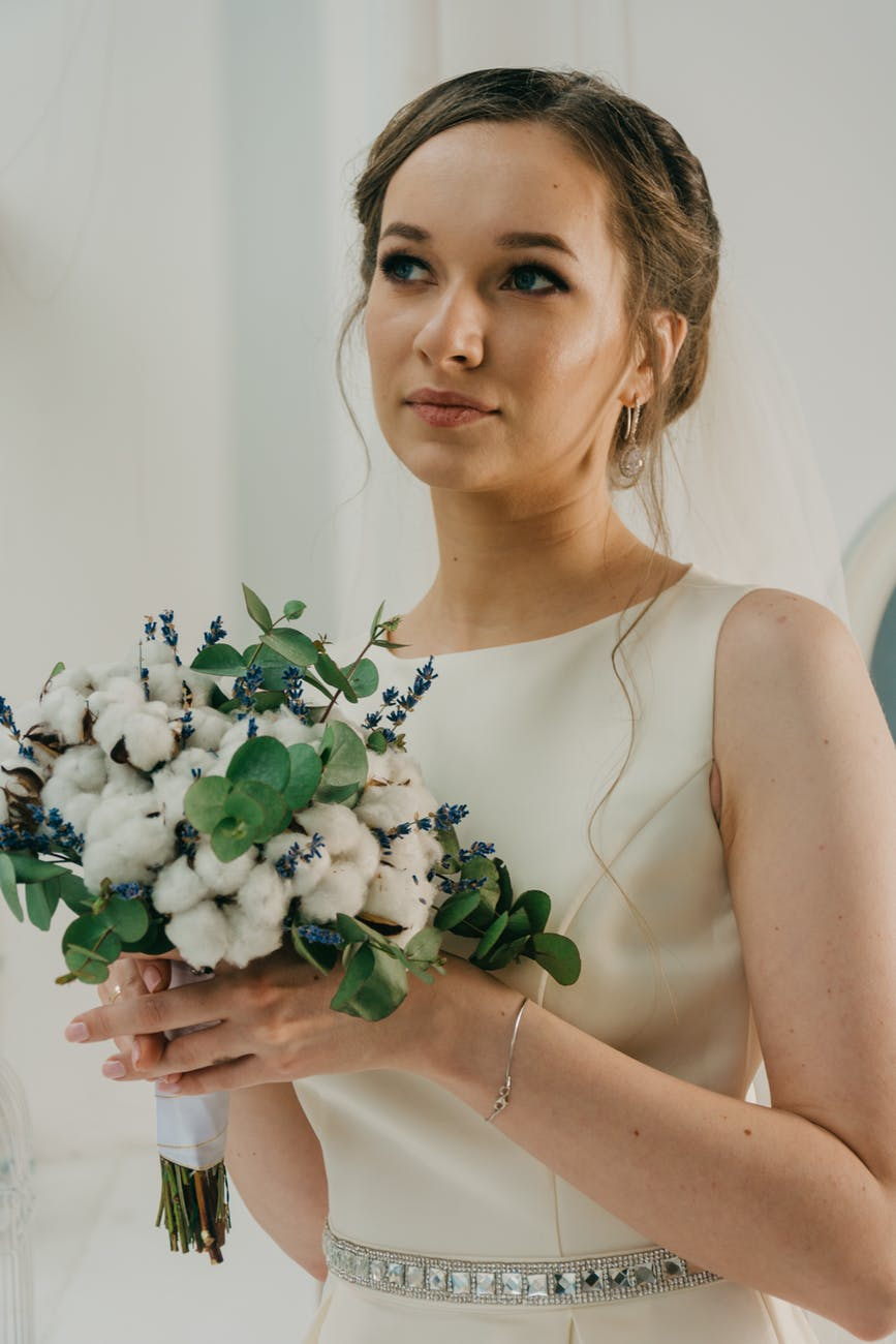 Bride holding hand tied with cotton bouquets