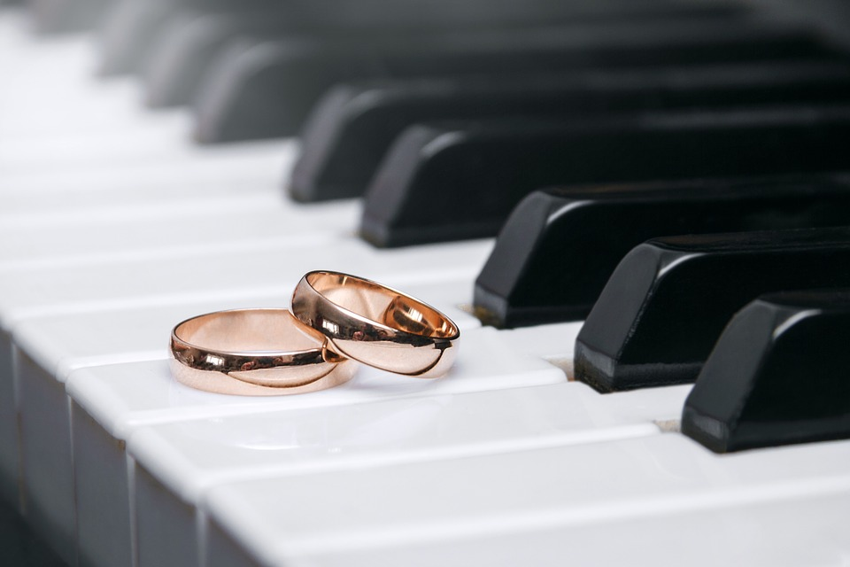Rose gold wedding bands on piano