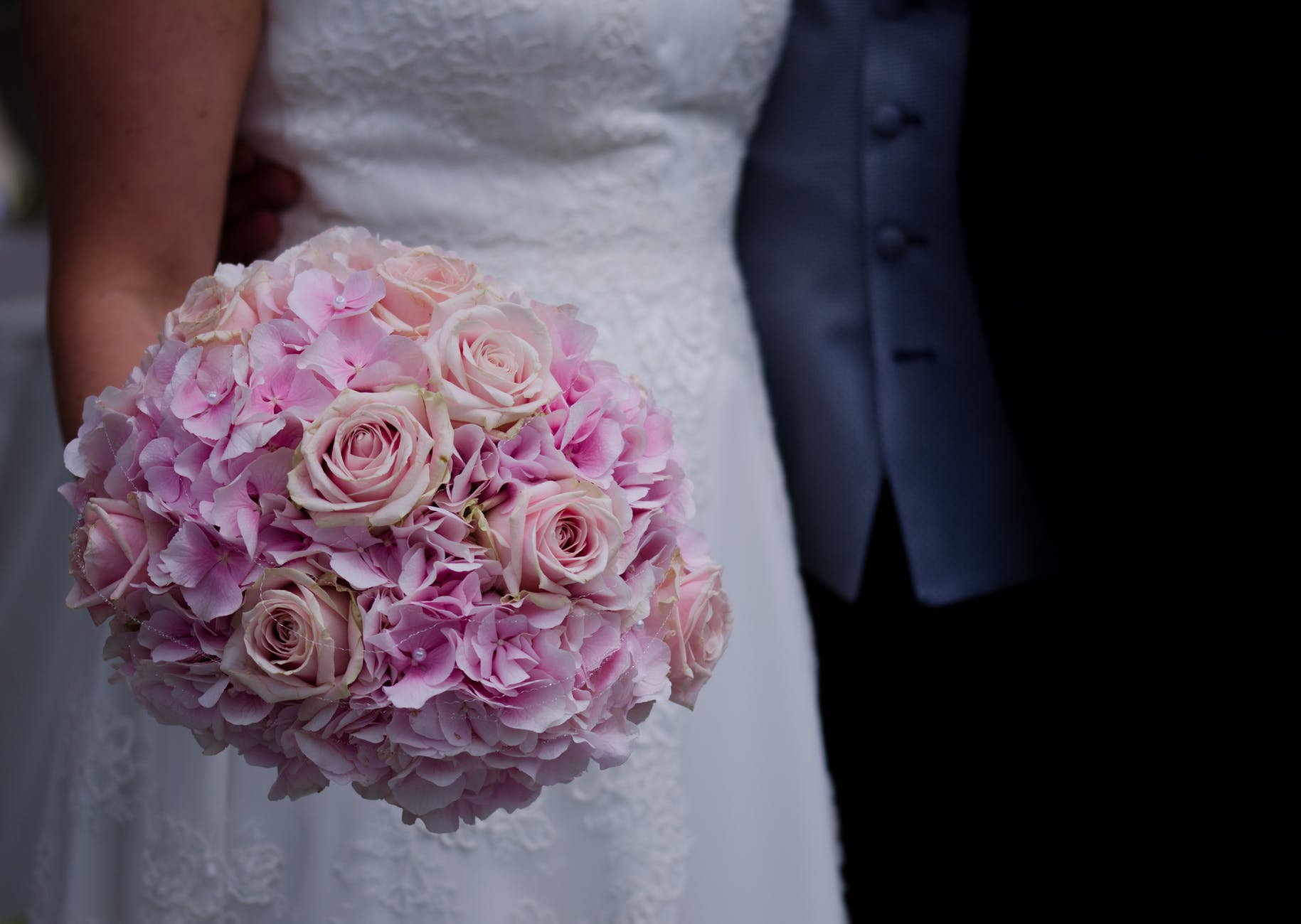 Bride holding round bouquet with roses