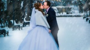 Couple kissing on the snow on wedding day