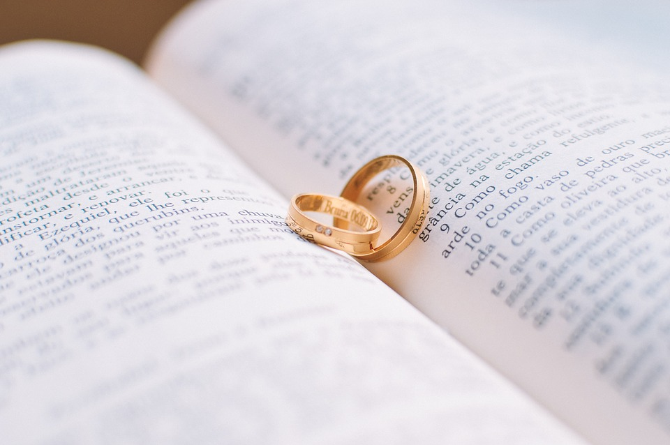 Yellow gold wedding band on pages of a open book