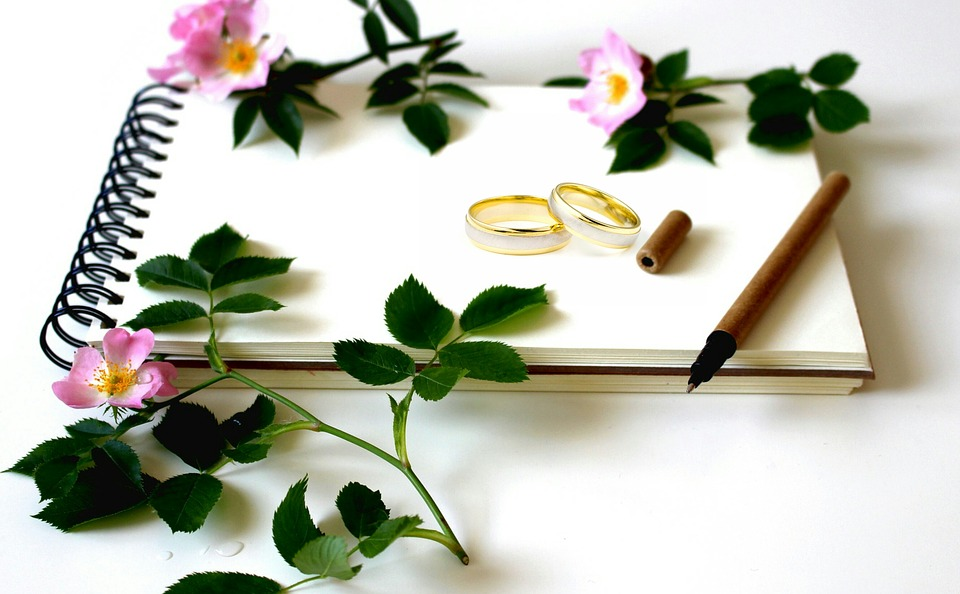 Wedding rings on a notebook next to a pen