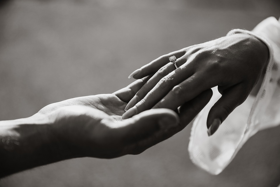 Groom's hand holding bride's hand