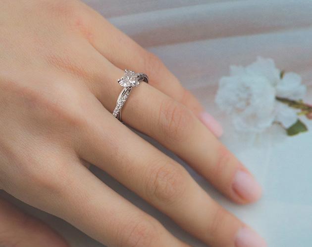 Girl wearing heart shape diamond engagement ring twisted shank setting