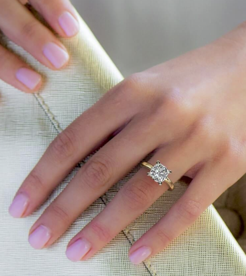 Cushion cut engagement ring on bride's finger