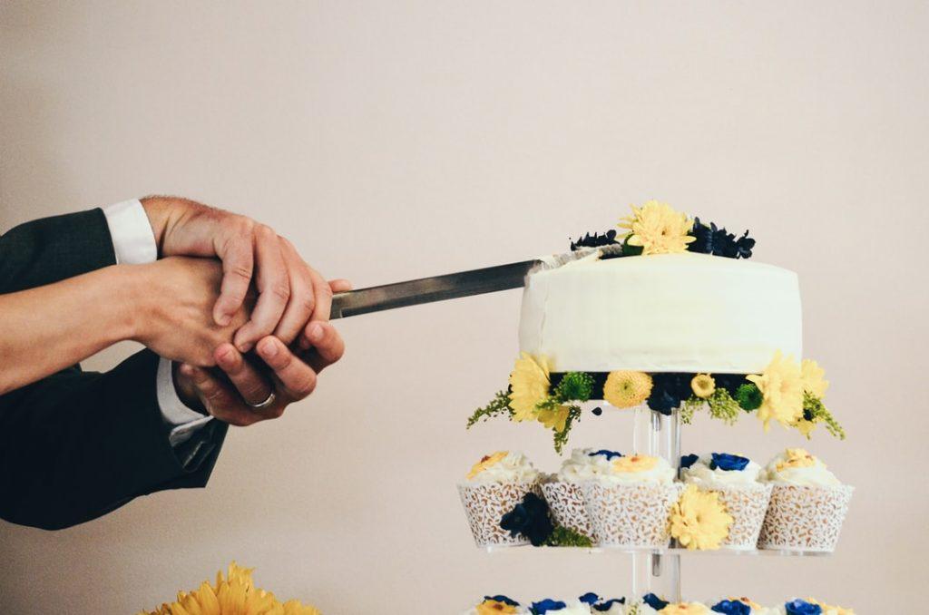 Couple cutting their wedding cake close up