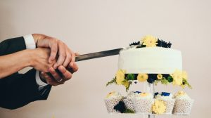 Couple cutting their wedding cake close up