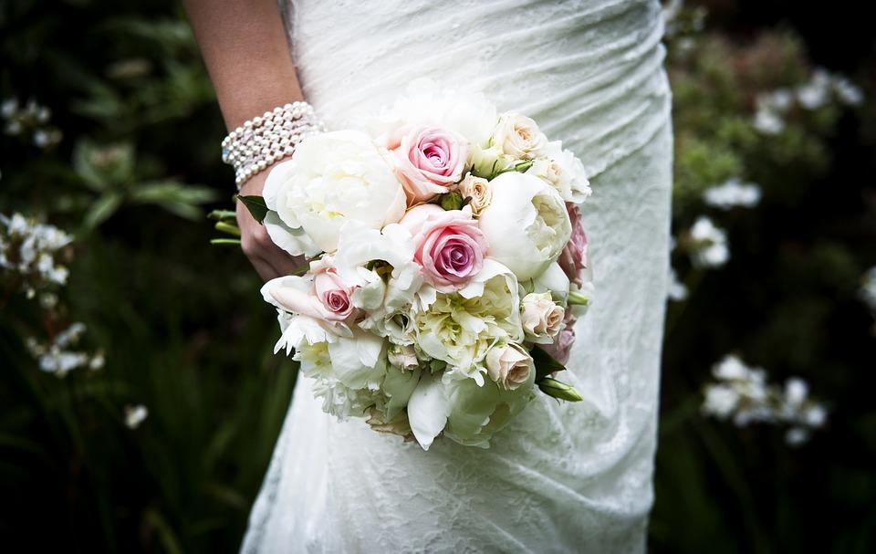 Bride holding peony bouquet