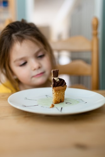 Little girl looking at a cake on plate