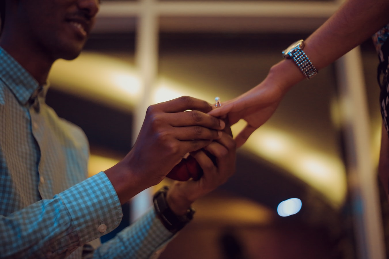Man putting a ring on her girlfriend's finger