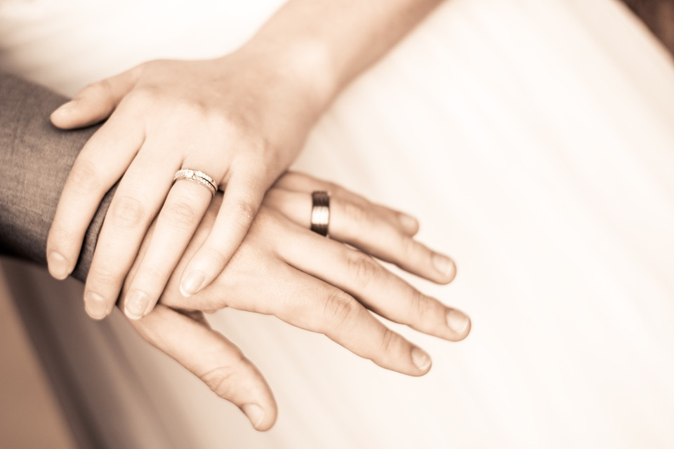 Bride and groom's hand wearing wedding ring