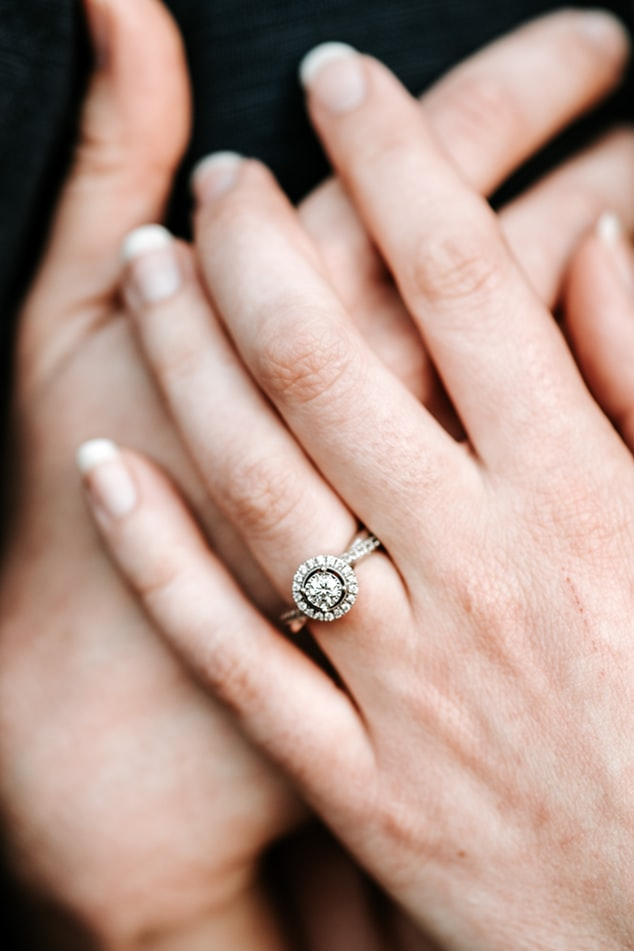 Synthetic diamond engagement ring on bride's finger closeup
