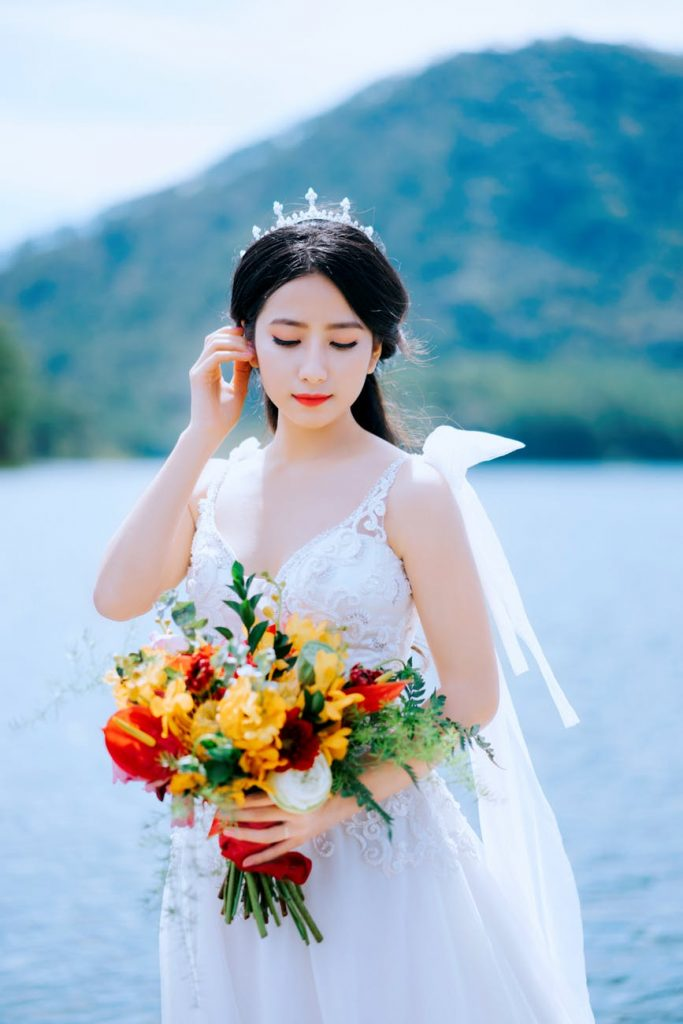 Asian bride in white dress holding flowers