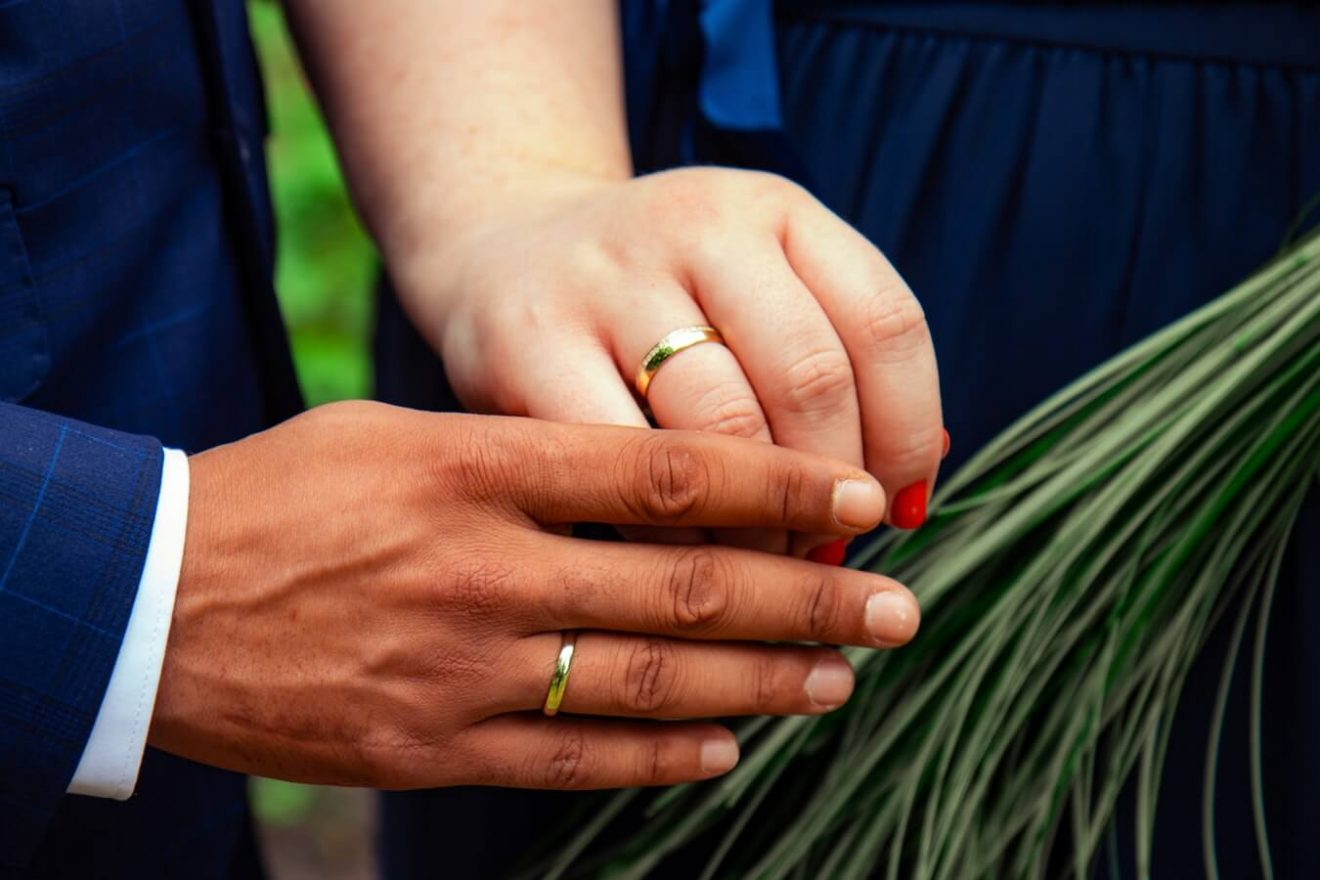 Couple wearing brass wedding rings
