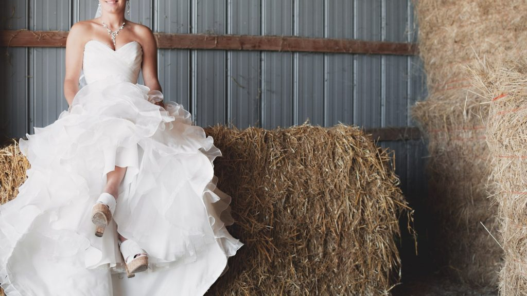 Bride sitting on haystack showing her shoes