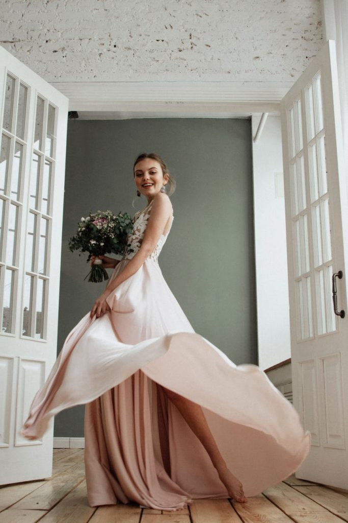 Fair skinned bride wearing salmon color dress