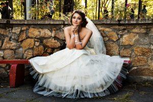 Bride in her wedding dress sitting on a park