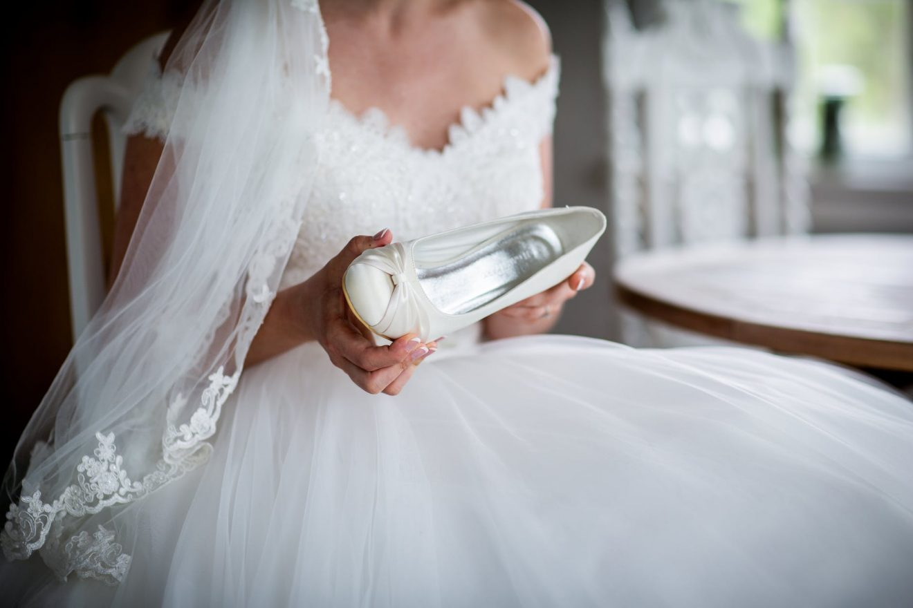 Bride in wedding dress holding her shoes