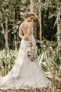 Bride in long sleeve wedding dress thinking about the pros and cons of long sleeve dress