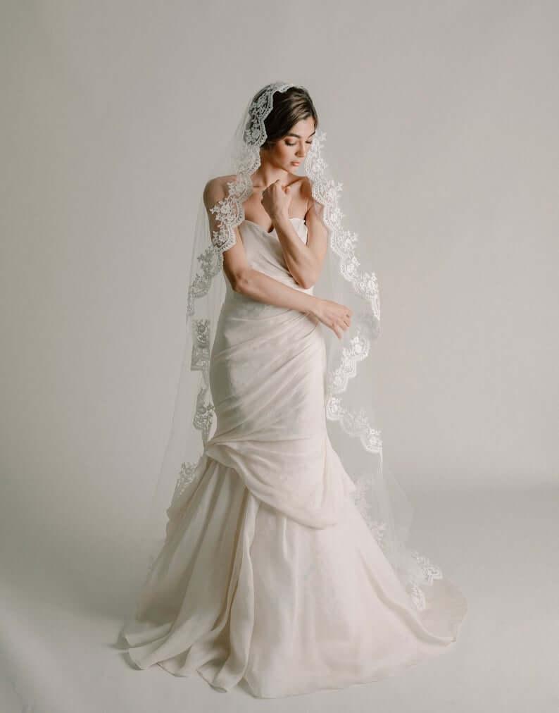 Bride wearing mantilla veil with white trumpet dress