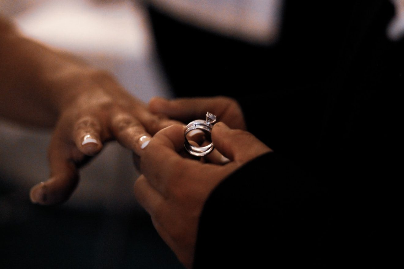 Man putting engagement ring on her girlfriend's finger