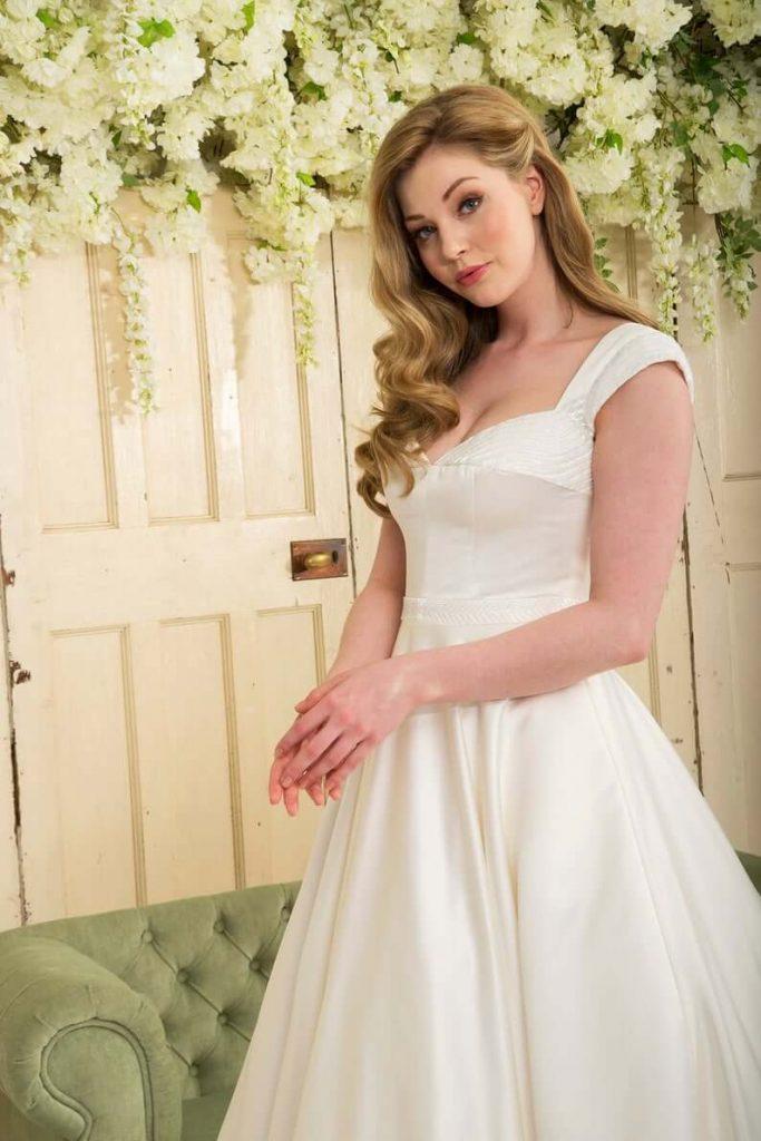 Bride wearing queen anne neckline dress white