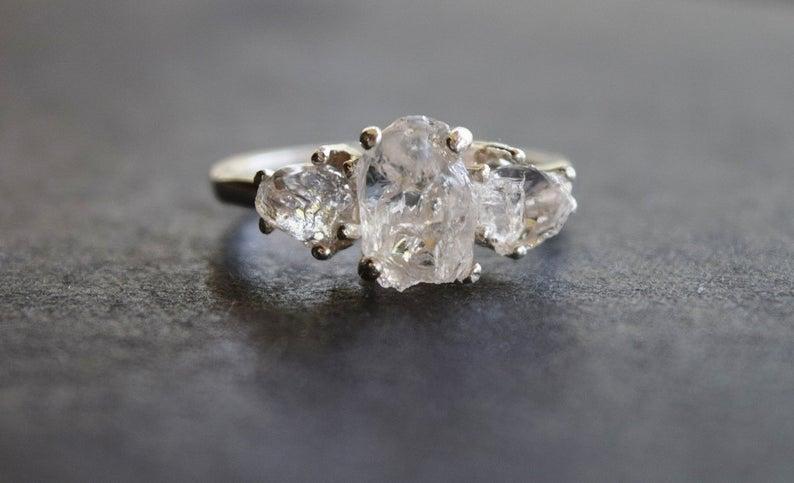 Raw diamond three stone ring close up in gray background