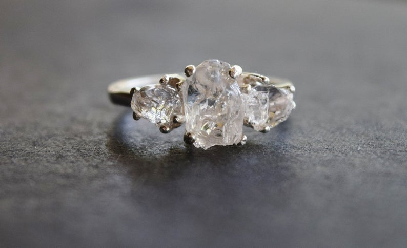 Raw diamond three stone ring close up in gray background