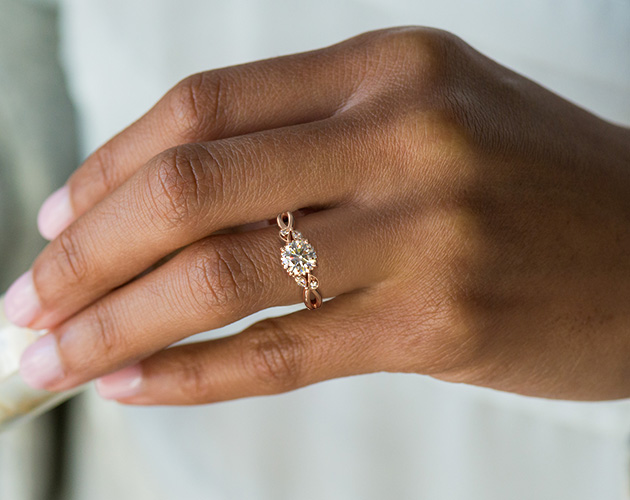 Rose gold engagement ring on dark skin tone