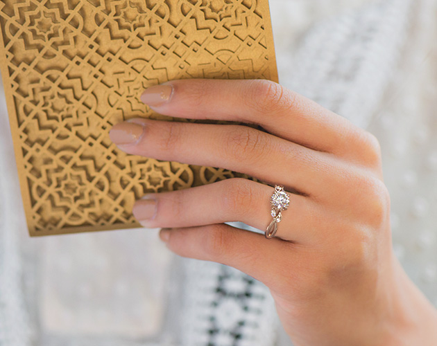 Rose gold engagement ring on white skin tone