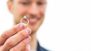 Groom holding lab-created diamond engagement ring