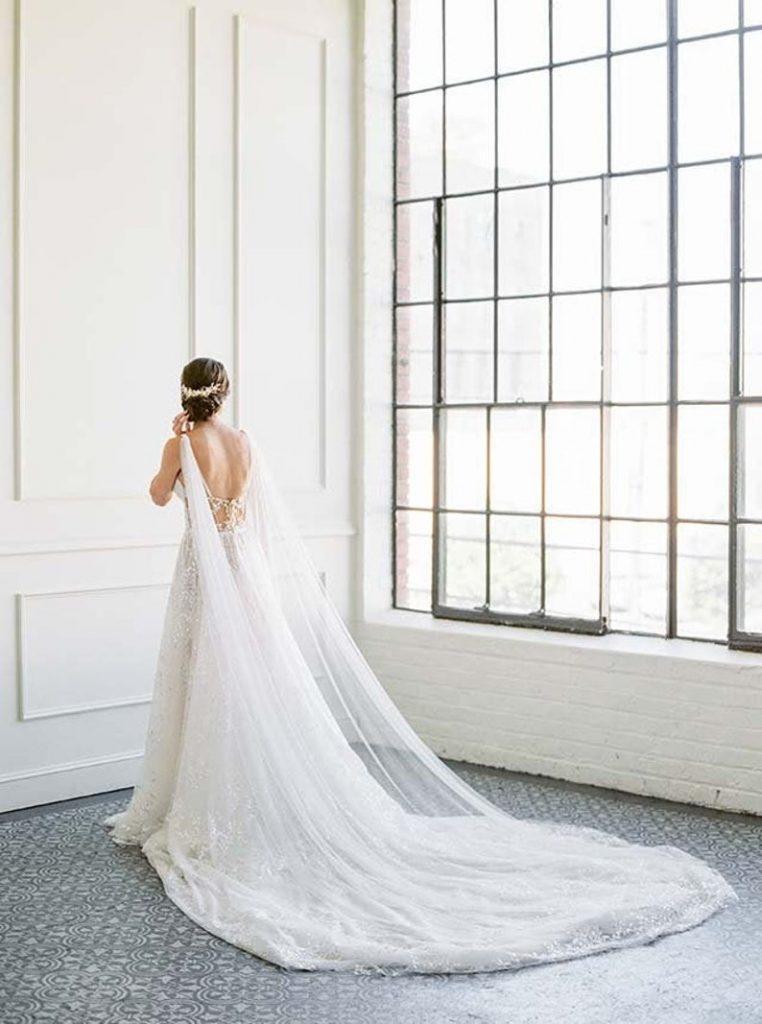 Bride wearing white shoulder cape as alternative for veil