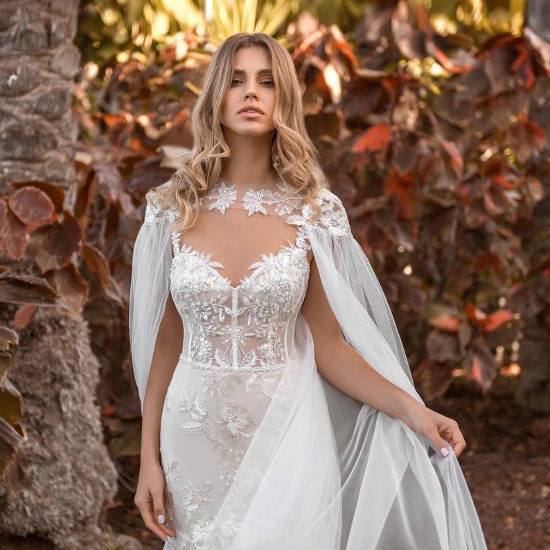 Beautiful bride wearing white wedding-cloak