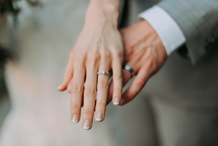 Couple's hand wearing white gold wedding rings