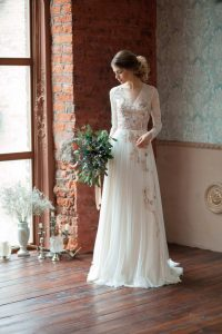 Young bride with long sleeved dress