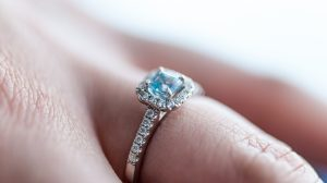 Bride wearing aquamarine engagement ring closeup on finger