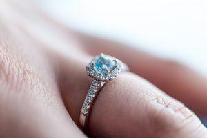 Bride wearing aquamarine engagement ring closeup on finger