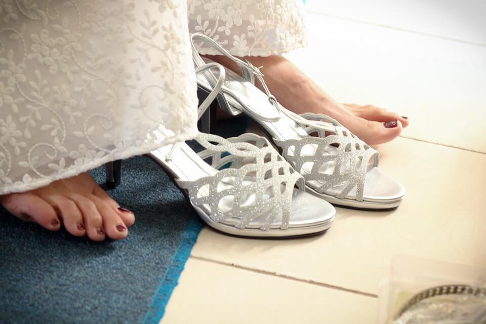 Bride wearing her wedding shoes