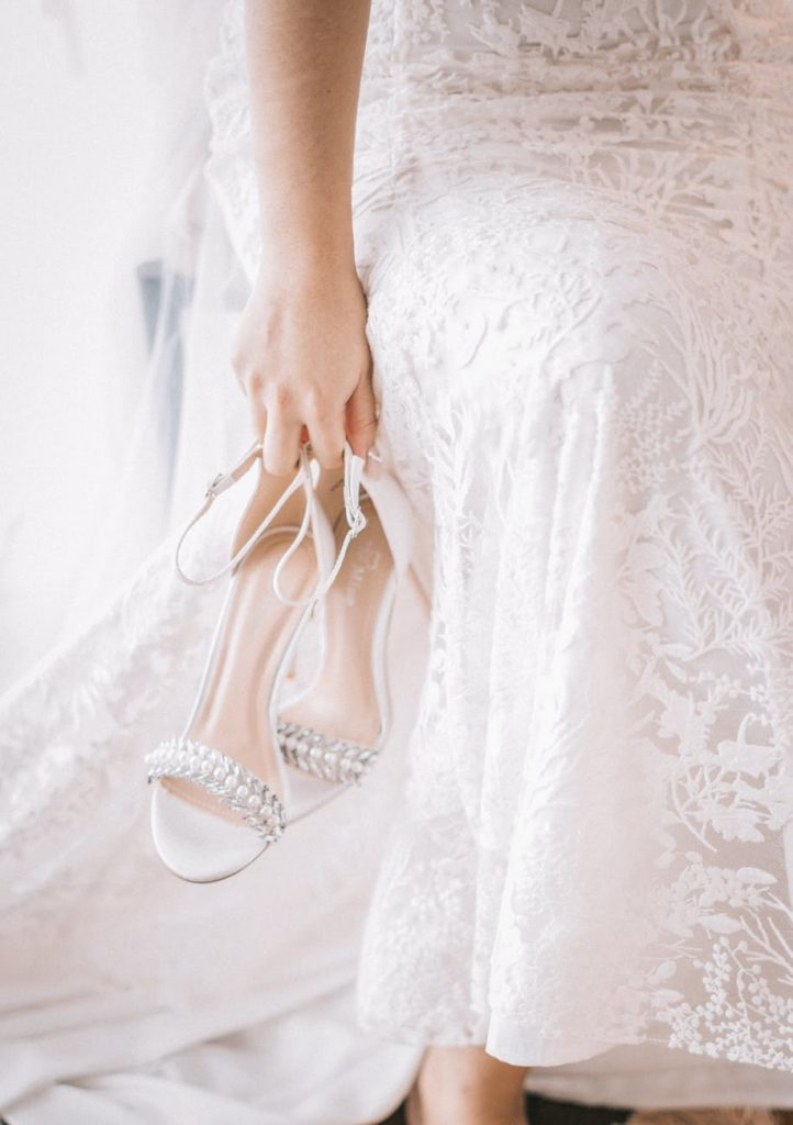 Bride holding her shoes in her hand
