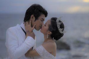 Bride wearing tiara kissing groom