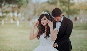 Groom fixing bride's dress