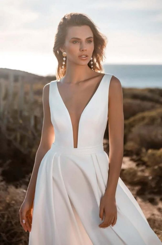 Bride wearing crepe minimalist gown at beach wedding
