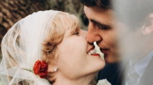 Bride wearing diamond stud kissing groom