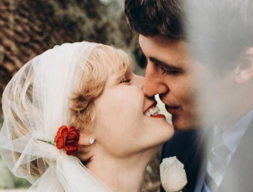 Bride wearing diamond stud kissing groom